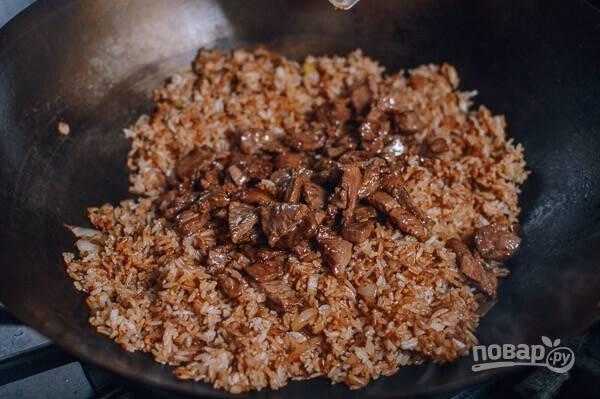 Отправьте к луку рис и разбейте комочки, если есть. Из оставшегося масла и соевого соуса сделайте заправку и влейте к рису, туда же отправьте говядину вместе с остатками маринада.