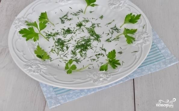 Зелень промойте. Немного нарвите её, уложите часть на дно салатницы.