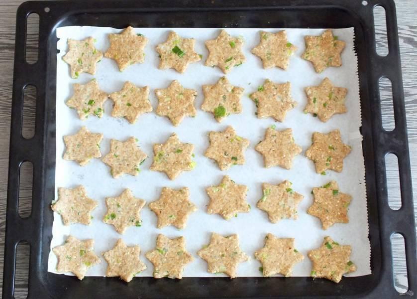 Переложите будущее печенье на противень застеленный пергаментной бумагой. Поставьте выпекаться в разогретую до 200 градусов духовку на 12-15 минут. Время зависит от толщины нарезанного печенья. Также учитывайте особенности своей духовки.
