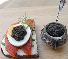 Чудесный бутерброд на ржаном хлебе с маслом и семгой, украшенный половинкой яйца с черной икрой подходит, чтоб совсем поразить воображение и вкус гостей.