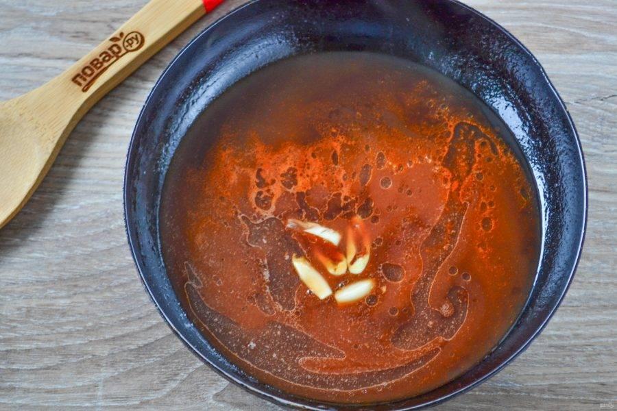 Пока готовятся крылышки, подготовьте соус. В сковороде смешайте соус чили, соевый соус, добавьте небольшой кусочек острого перца (без семечек!) и разрезанный на несколько частей зубчик чеснока. Выдавливать через пресс чеснок не нужно, поскольку нам необходимо, чтобы чеснок только лишь отдал свой аромат соусу. Уваривайте соус в течение 5 минут после закипания.
