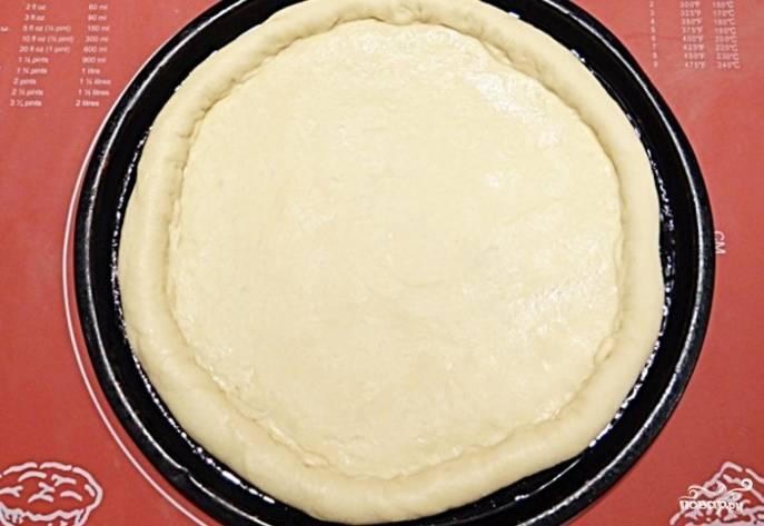 5. Переложите тесто на противень, предварительно смазанный маслом, и сформируйте из него (теста) бортик по краям коржа.