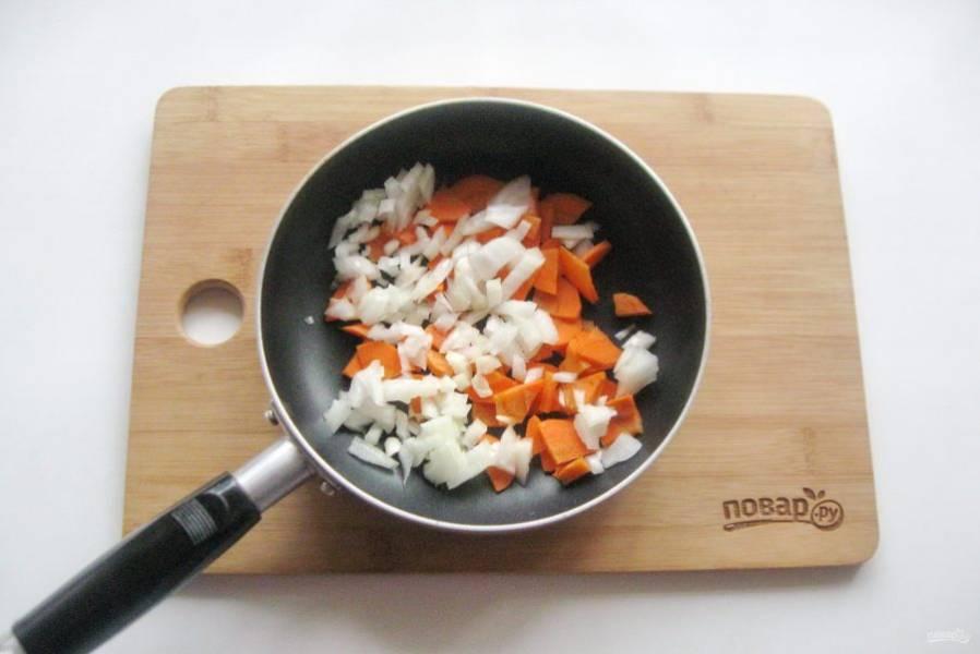 Морковь и репчатый лук мелко нарежьте, выложите в сковороду. Влейте рафинированное подсолнечное масло, припустите овощи на небольшом огне в течение 7-8 минут.