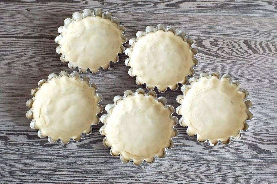 Возьмите формы для кексов.  Смажьте тонким слоем сливочного масла. Каждую заготовку вложите в формочку. Распределите по ней, прижимая к бортикам и дну формочки.