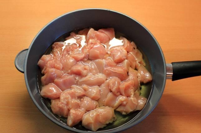 Разогреваем в сковороде растительное масло и выкладываем порезанное куриное филе. Солим и перчим по вкусу.