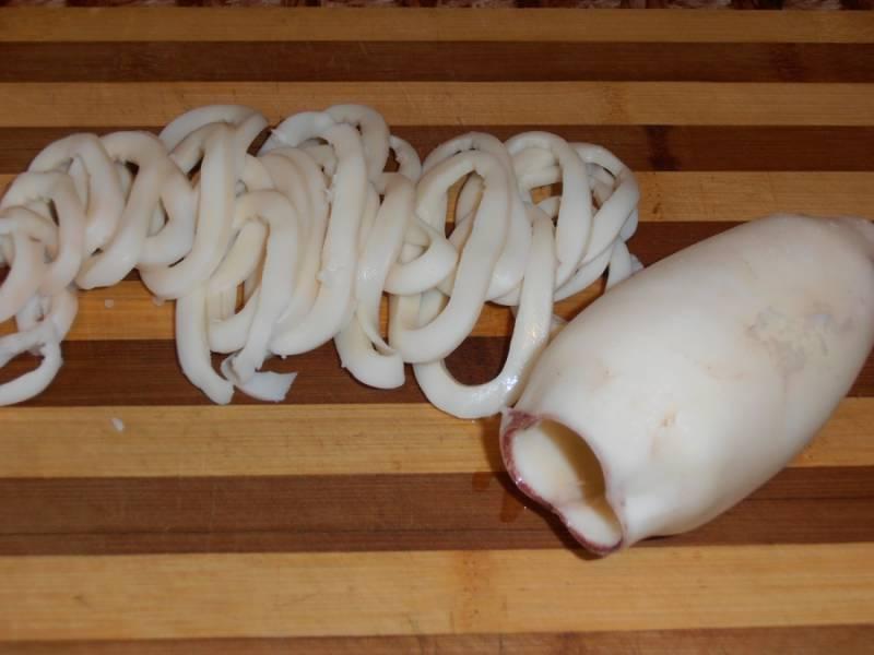 1. Начинаем с самого главного - подготовки овощей и морепродуктов. Итак, отвариваем кальмары не более 2 минут в подсоленной воде и параллельно отвариваем овощи в мундире. Когда все ингредиенты будут готовы и остынут, приступаем к нарезанию. Кальмары следует сначала нарезать кольцами.