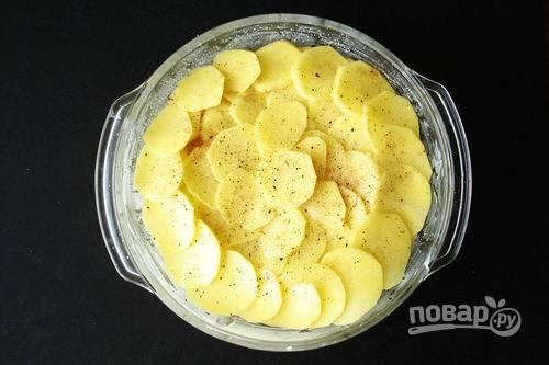 Смазываем форму для запекания сливочным или растительным маслом. Картофель нарезаем тонкими пластинками и смешаем с измельченным чесноком, выкладываем картофель в форму, посыпая слои солью, перцем и специями.