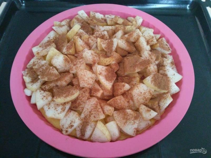 Выложите тесто на дно подготовленной формы, разровняйте его при помощи ложки или лопатки. Сверху разложите груши, посыпьте их корицей. Выпекайте пирог в разогретой до 180 градусов духовке в течение 25-30 минут.