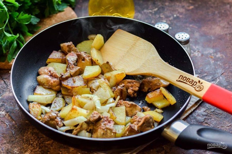 Жарьте печень, картофель и лук на небольшом огне 15 минут, периодически помешивая все ингредиенты лопаткой. В конце приготовления приправьте все солью и перцем по вкусу. При подаче посыпьте блюдо любимой рубленой зеленью.