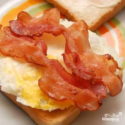 2. На жире от бекона поджарьте яйцо. Из белого хлеба сделайте тосты (в тостере), смажьте его маслом или сливочным сыром. Положите жареное яйцо, бекон.