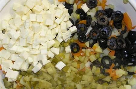 Режем кубиками огурцы и сыр, засыпаем в миску. Маслины нарезаем колечками.
