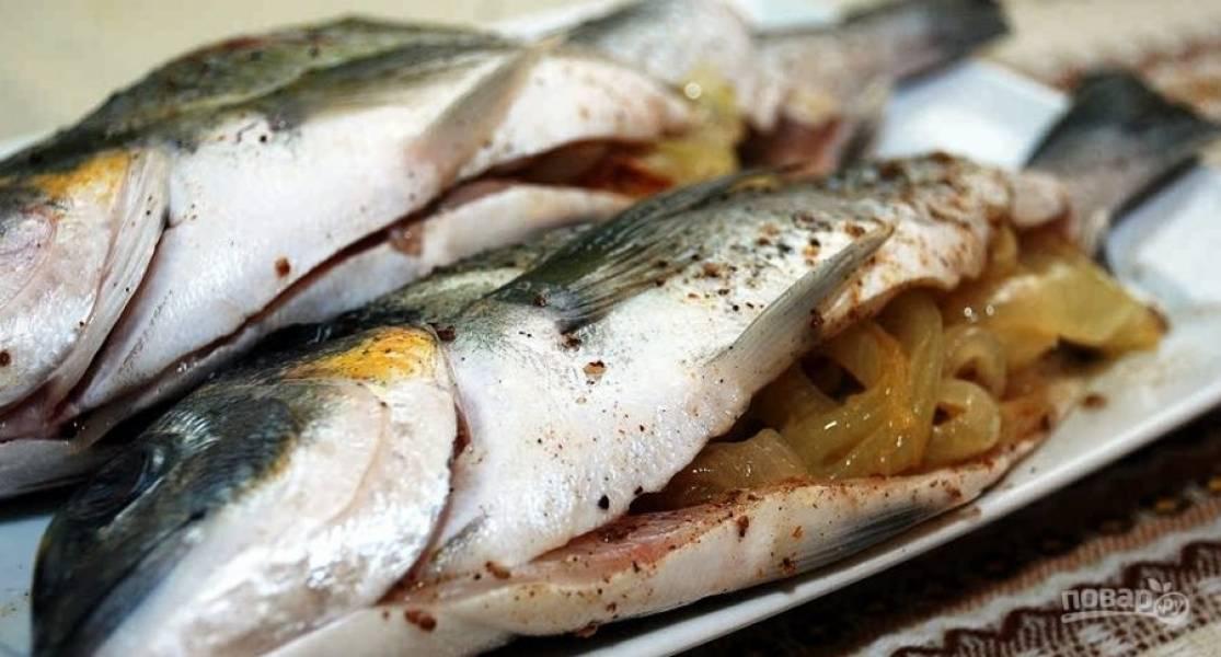 1. Рыбу разморозим и разделаем. Пока она размораживается, лук порежем кольцами и обжарим на масле до румяности. Затем фаршируем рыбу. Специи — по вкусу.