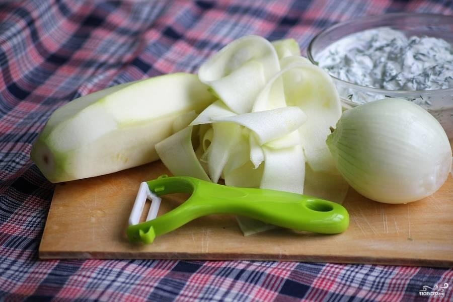 Приготовьте начинку: кабачки помойте, почистите и с помощью специальной овощечистки нарежьте на тонкие полоски. Лук порежьте кубиками.
