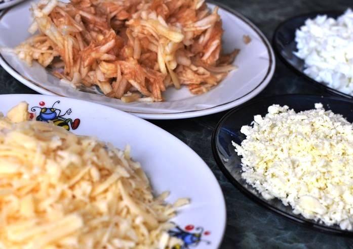 Отдельно натрите желтки и белки отваренных яиц, а также очищенные яблоки и сыр.