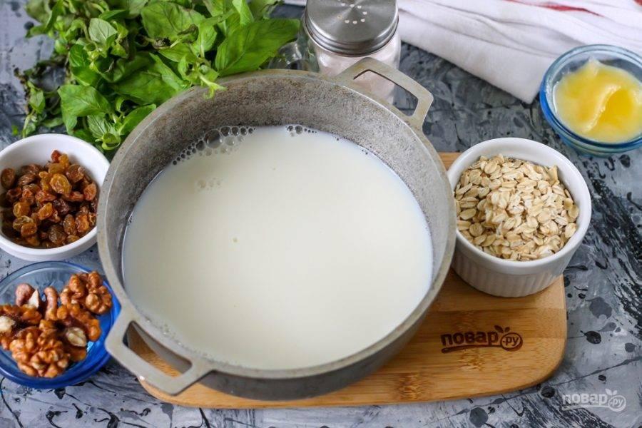 В казан или кастрюлю с антипригарным дном влейте молоко любой жирности. Поместите емкость на плиту и доведите до кипения, присолите и убавьте нагрев до минимального.