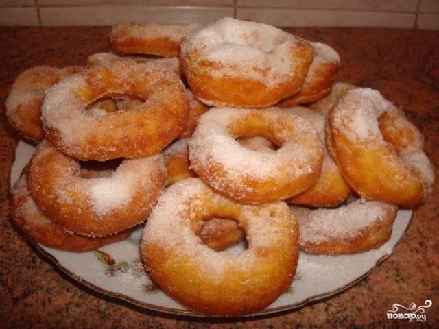 Готовые пончики выкладывайте на тарелку, покрытую салфеткой или бумажным полотенцем, уложенный в несколько слоёв. Так с пончиков стечёт лишнее масло. Когда пончики немного остынут, их можно присыпать сахарной пудрой.