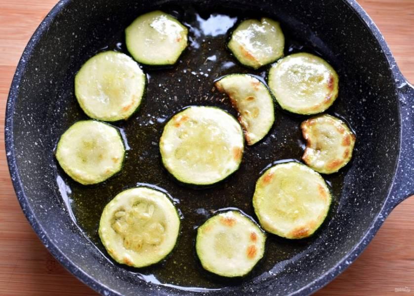 Цукини нарежьте тонкими кружочками. Обжаривайте порциями на разогретом масле до легкой корочки. Выкладывайте на тарелку.