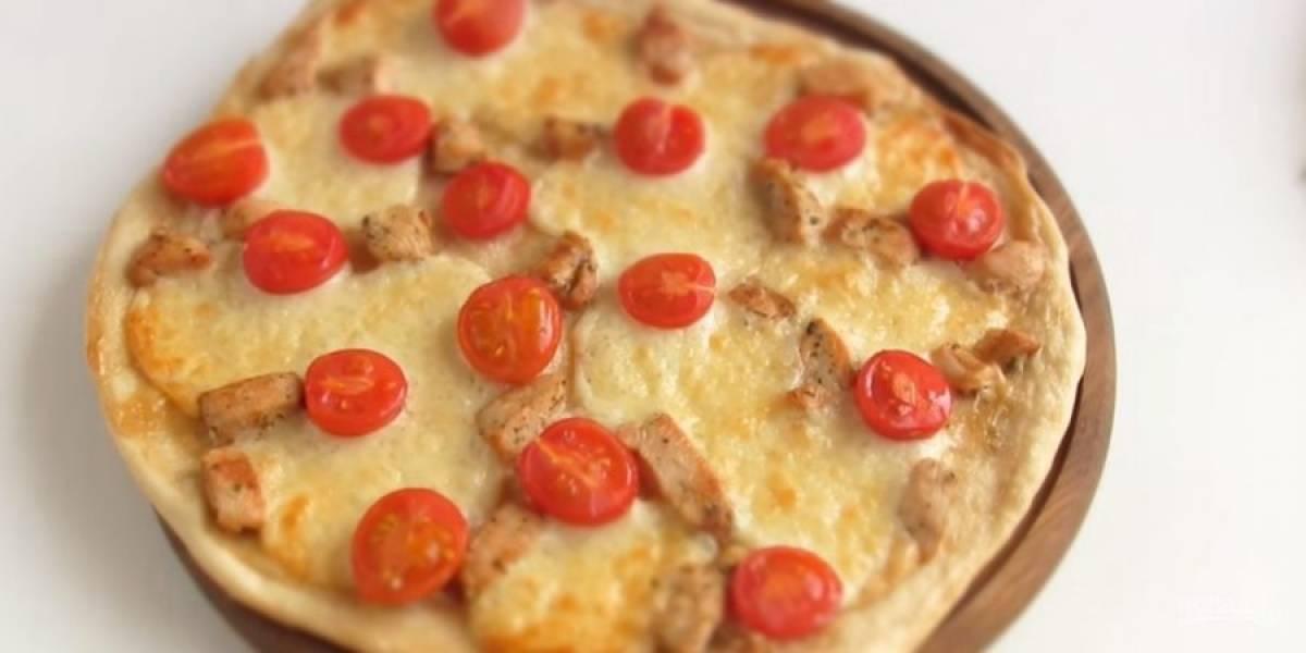 5.  Смажьте тесто соусом, выложите нарезанную пластинками моцареллу, обжаренную курицу и помидоры, разрезанные на небольшие части. Выпекайте в разогретой до 200 градусов духовке в течение 15-20 минут.