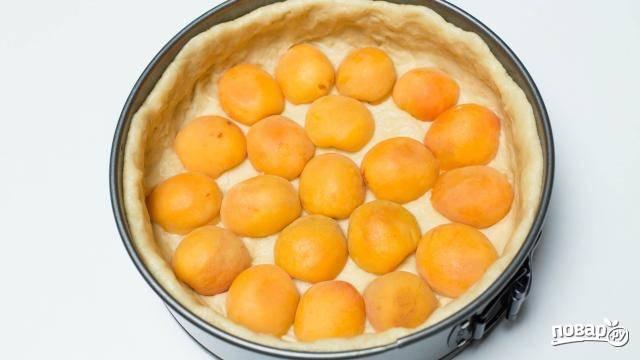 10. Достаньте корж из холодильника. Если используете фрукты, то выложите их ровным слоем. В данном случае это абрикосы, предварительно разделенные половинками.