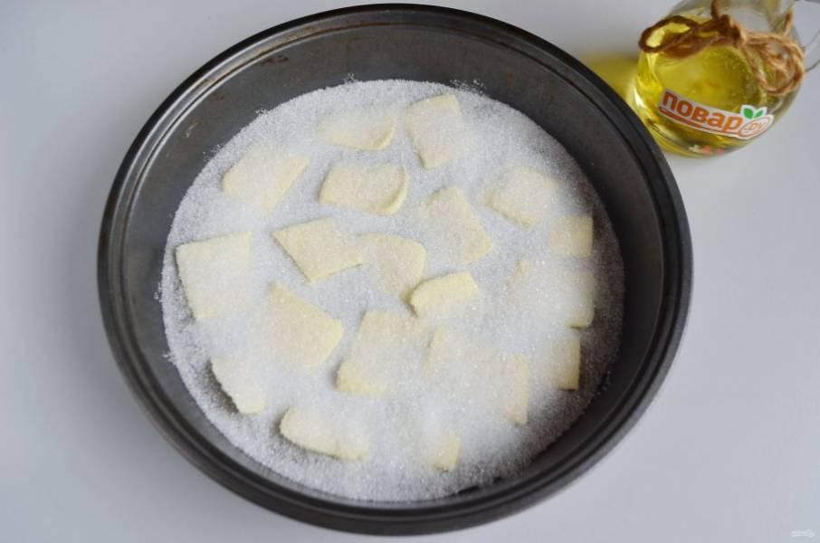 2. Застелите дно бумагой для выпечки. Смажьте ее сливочным маслом, сверху положите ломтики холодного масла, посыпьте половиной стакана сахара.