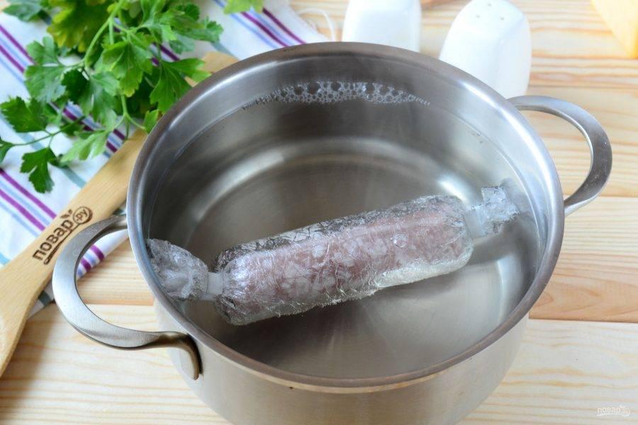 В небольшой кастрюльке вскипятите воду, в кипяток отправьте куриную колбаску, варите 30-40 минут. Готовую колбаску выньте из воды и охладите прямо в пленке, не разворачивая.