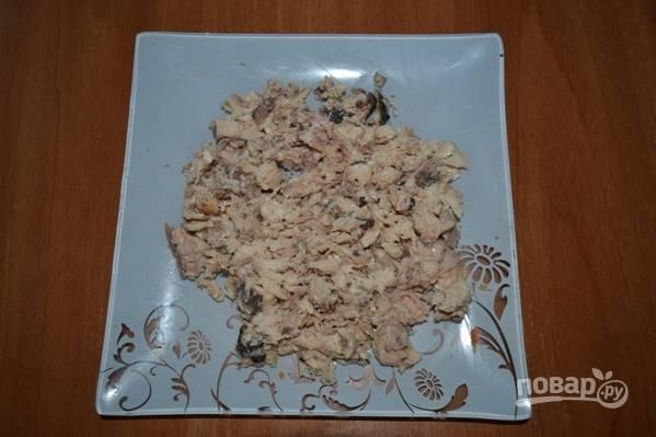 Консервированную горбушу нужно порезать ножом на небольшие кусочки и отправить в кастрюлю к овощам и рису.