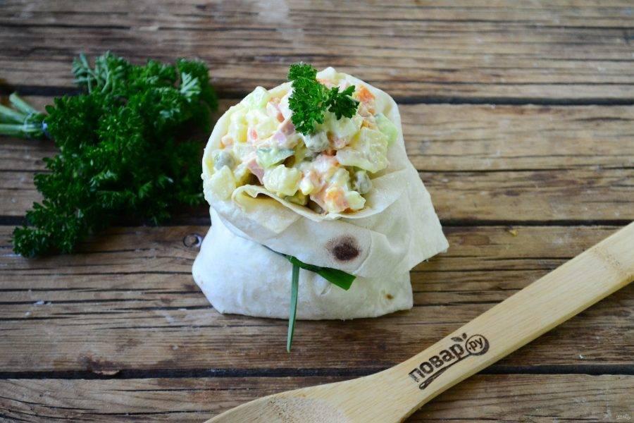 На лист лаваша положите несколько столовых ложек салата, подверните края с трех сторон и закрепите пером лука или чеснока, чтобы получился мешочек. В таких мешочках очень удобно подавать салаты порционно. Приятного аппетита!