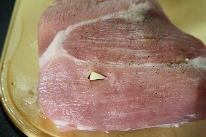Кусок окорока помойте, обсушите. Зубчики чеснока нарежьте маленькими дольками. Нашпигуйте мясо дольками чеснока. Для этого ножом проделайте небольшие отверстие и положите в них дольки чеснока.