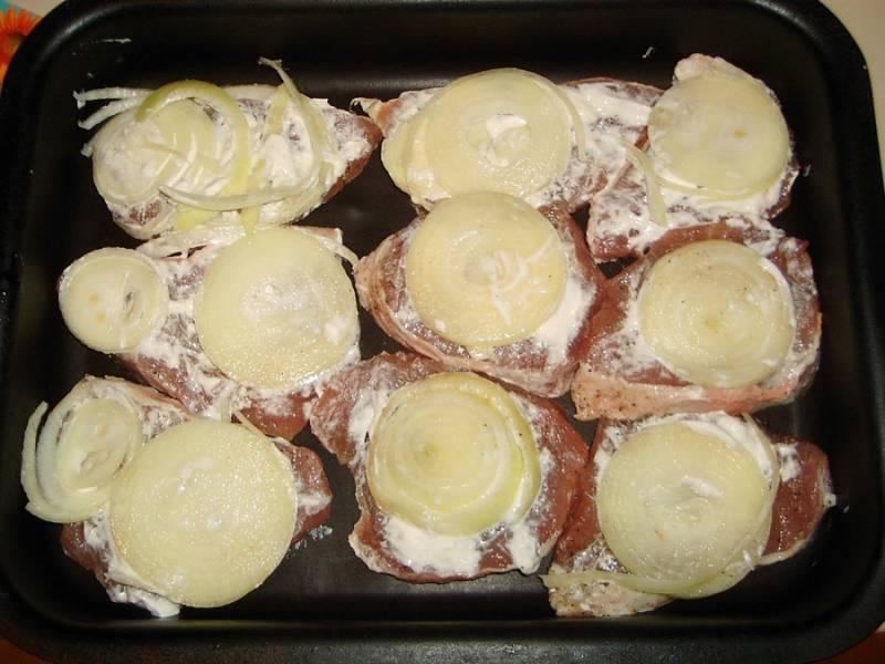2. Противень или форму для запекания смазать немного растительным маслом и выложить отбивные. Подсолить и поперчить по вкусу, смазать немного майонезом или сметаной. Очистить луковицу и нарезать кольцами. Выложить сверху мяса по 1-2 кусочка.