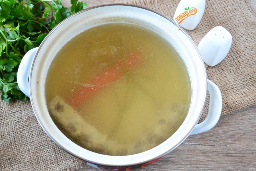 Ребрышки из бульона извлеките, мясо необходимо будет отделить от кости и добавить в суп по желанию в конце приготовления. Также из бульона нужно извлечь морковь, лук и веточки петрушки. Сам бульон можно процедить. Такой бульон можно замораживать и хранить в течение нескольких месяцев.