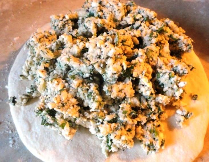На каждую лепешку выложите часть начинки, края теста соберите в виде шара и закрепите края вверху. Теперь каждый шар аккуратно расплющите ладонью в плоский пирог. Сверху сделайте небольшое отверстие для выхода пара и отправьте выпекаться в разогретую до 200 градусов духовку на 20 минут. Горячий пирог смажьте сливочным маслом и подайте на стол.