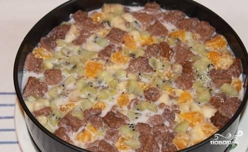 И приступим к сборке торта. На дно формы выкладываем корж, на него выкладываем смесь из фруктов и кусочков коржей с йогуртом.
