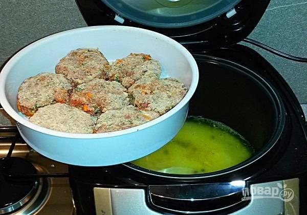3. В чашу мультиварки всыпьте рис, добавьте воду и специи. Установите котлетки сверху.