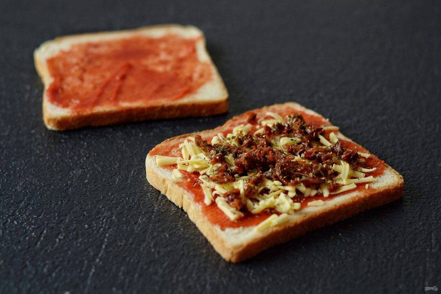 Сверху равномерно выложите вяленые томаты. Посыпьте итальянскими травами и накройте бутерброд второй половинкой хлеба.