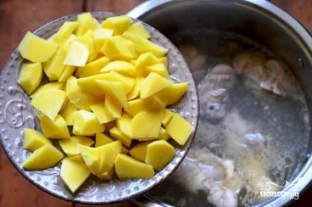 Окорочок поделим на несколько частей и отправим варится в 4 литрах воды. Не забудьте снять пену. Через 10 минут добавляем очищенный и нарезанный небольшими кубиками картофель.