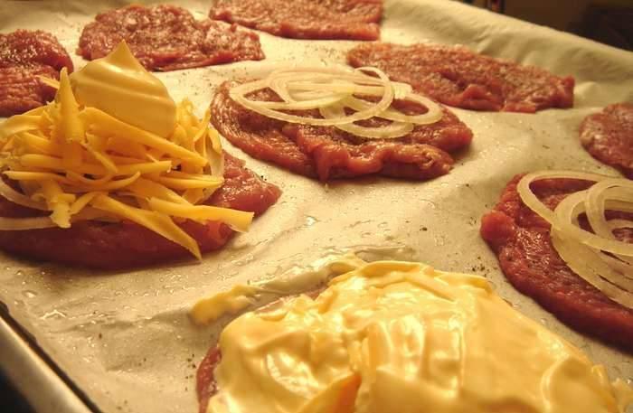Выкладываем мясо на противень, солим и перчим. Кладем на мясо лук, порезанный полукольцами. Сверху присыпаем тертым сыром и обильно поливаем майонезом. Запекаем в духовке, прогретой до 180 градусов. Готовим мясо до хрустящей золотистой корочки.