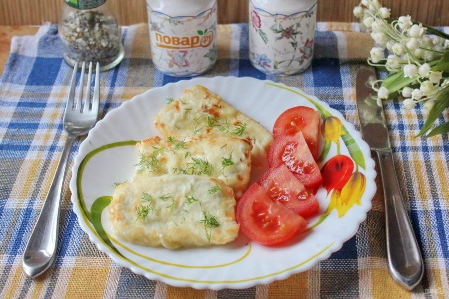 Жареный сыр выложите на тарелку. Подавайте саганаки по-гречески в горячем виде с зеленью и свежими помидорами.