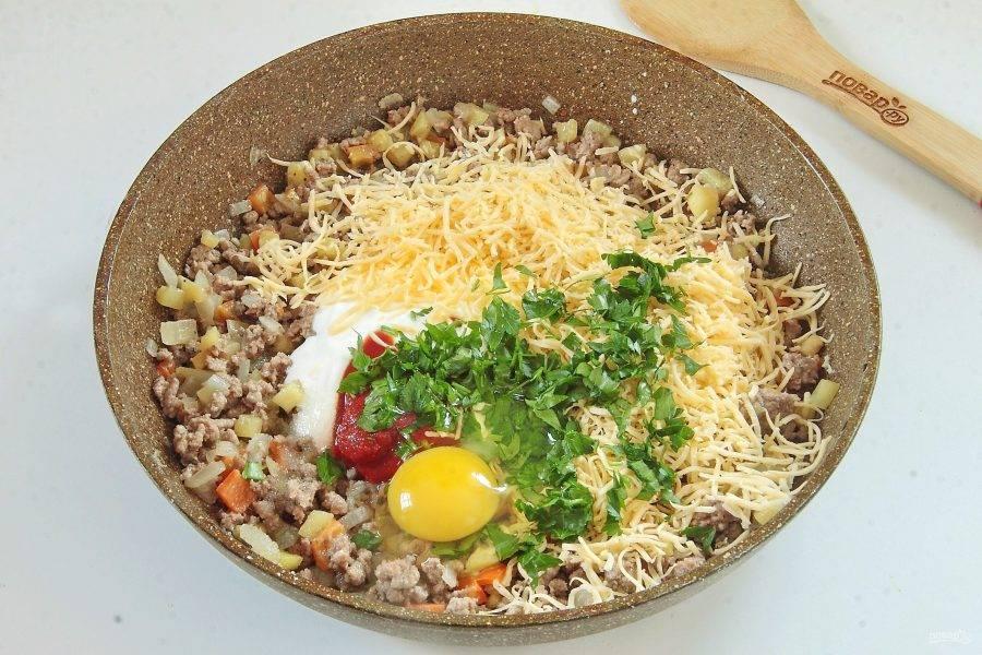К остывшей начинке добавьте тертый сыр, сметану, томатную пасту, сахар, соль и черный молотый перец. Вбейте яйцо и добавьте измельченную зелень.