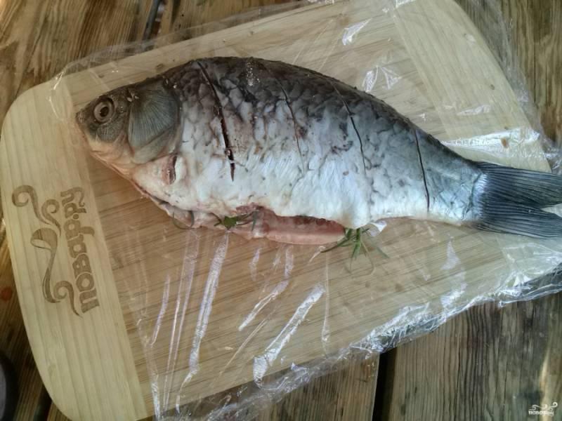 Рыбу почистите, выпотрошите, удалите плавники, сделайте на боку несколько косых надрезов. Поперчите и посолите по вкусу, добавьте зелень внутрь рыбы.