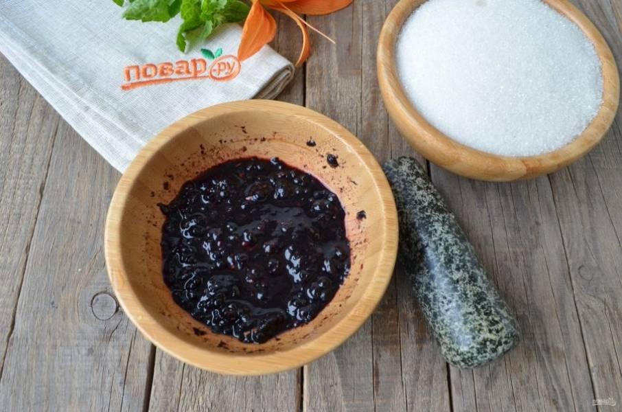 Возьмите ступку или просто удобную глубокую посудину и тяжелый пестик. Не большими порциями насыпайте ягоды и давите, растирайте пестиком, чтобы образовалась кашица. Добавьте сахар, перемешайте и оставьте на 2-2,5 часа варенье. За это время нужно несколько раз его перемешать, чтобы полностью растворить сахар.