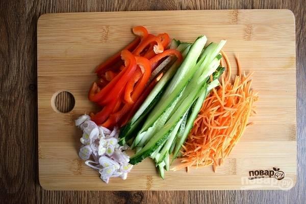 Перец и огурец нарежьте тонкими ломтиками, морковь натрите на корейской терке, лук нашинкуйте.