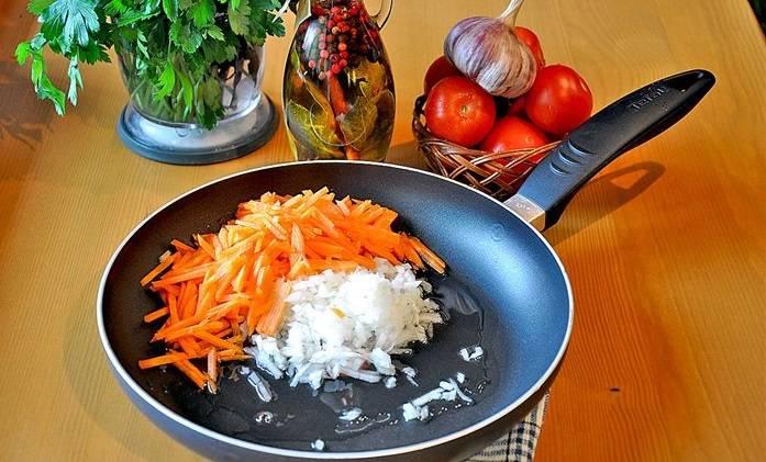 Тем временем мелко нарежьте лук, морковь режем соломкой. Несколько минут обжармваем овощи на растительном масле, затем добавляем измельченный чеснок и перец чили. Жарим еще 5 минут.