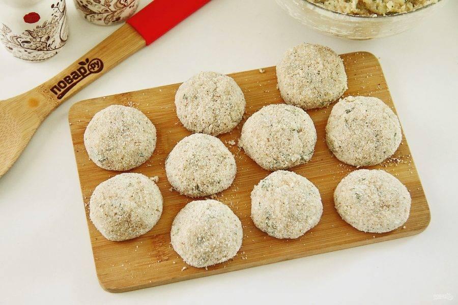 Сформируйте из приготовленного фарша небольшие шарики, размером примерно с грецкий орех и обваляйте их в сухарях.