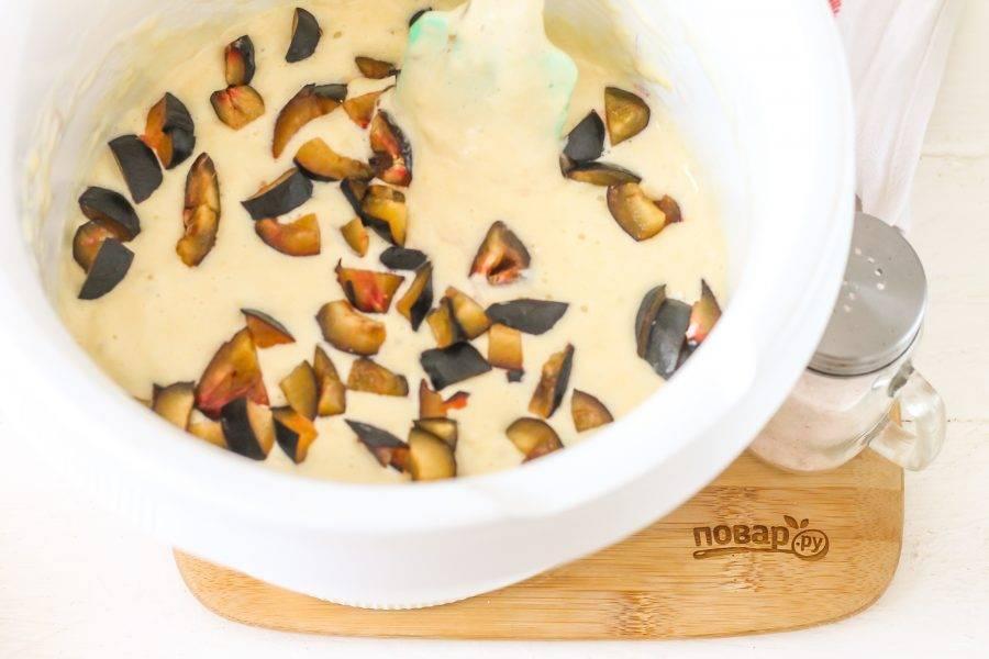 Разогрейте духовку до 180 градусов. Промойте сливы и располовиньте их, удалите косточки. Нарежьте половинки фруктов мелкими кубиками и добавьте в тесто. Нарежете крупно и нарезка опустится на дно при выпекании десерта.