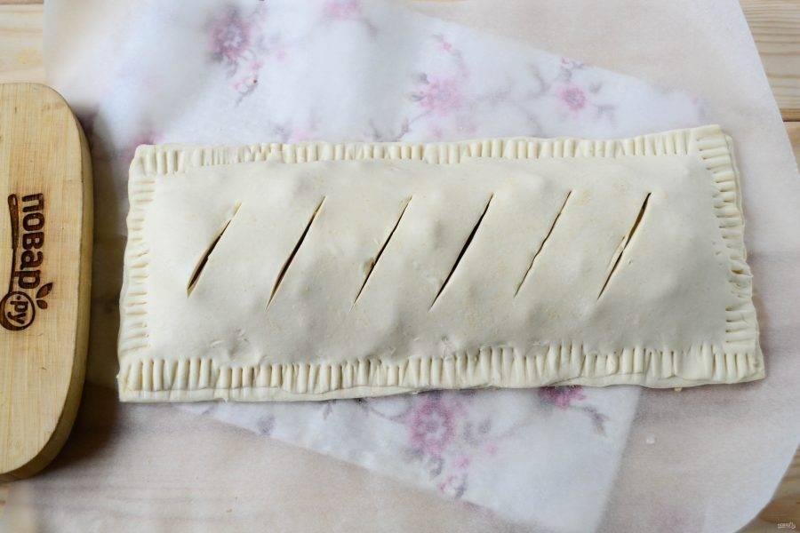 Накройте сверху вторым прямоугольником теста и закрепите края вилкой. Сверху сделайте несколько надрезов.