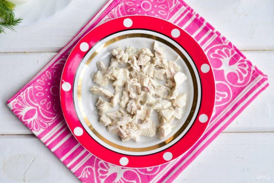 Отварное куриное филе нарежьте на кубики и выложите на блюдо.