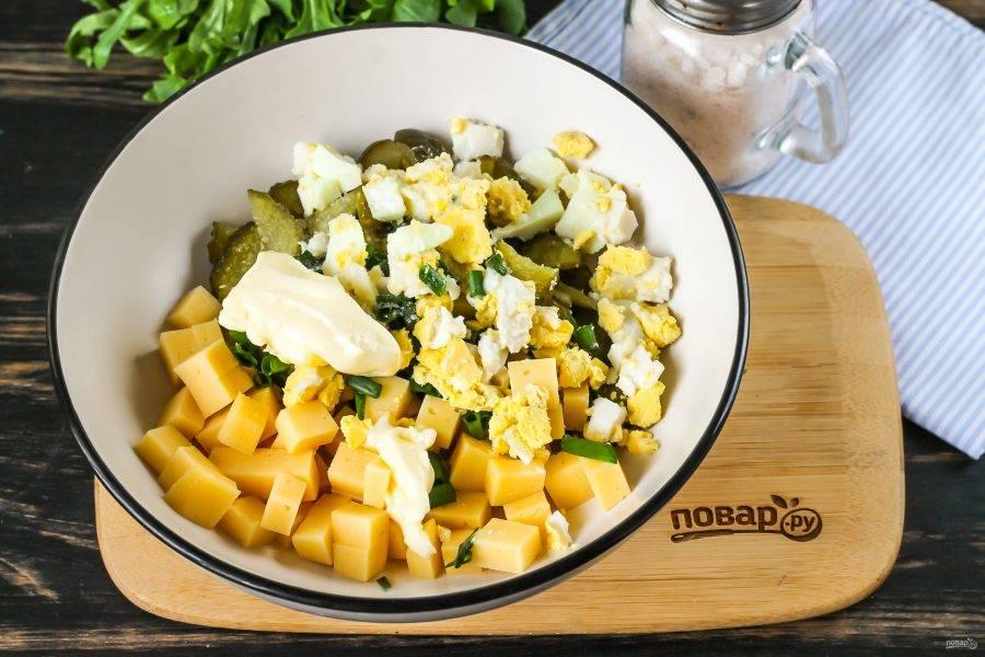 Очистите отварное куриное яйцо от скорлупы, промойте и нарежьте мелким кубиком. Добавьте в емкость вместе с майонезом любой жирности. Посолите и перемешайте салат.