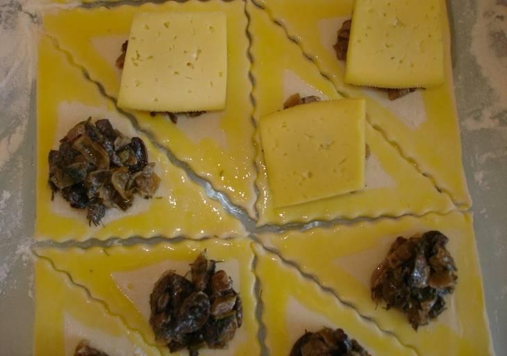 Желток смешиваем с небольшим количеством воды и смазываем этой смесью края каждого треугольника. В середину треугольника кладем 1-1,5 чайную ложку грибной начинки и накрываем ее кусочком сыра.