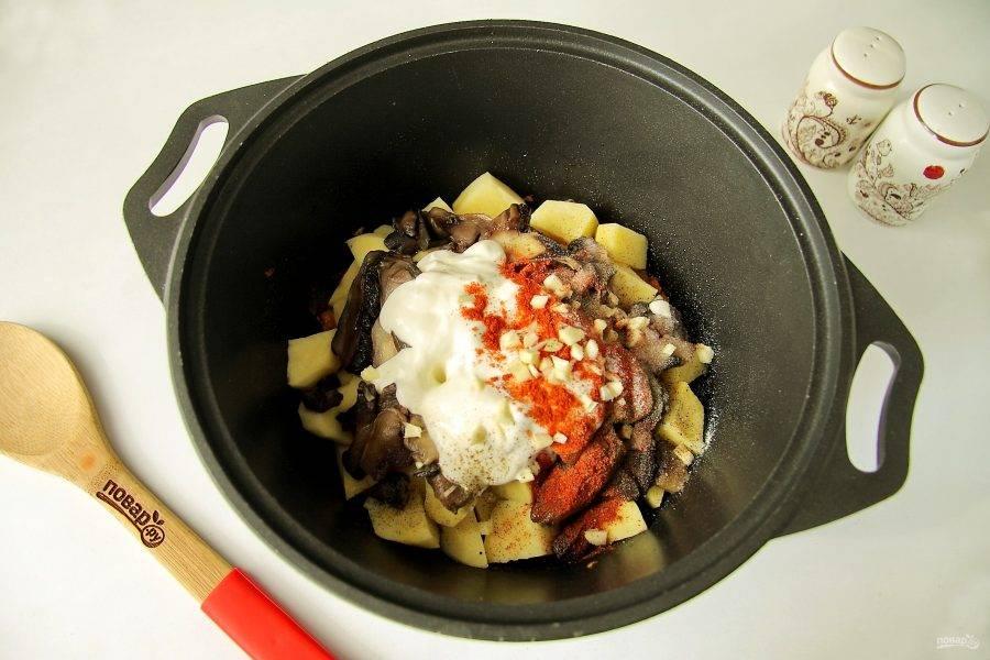 Добавьте сметану, измельченный ножом чеснок, посыпьте все солью и специями.