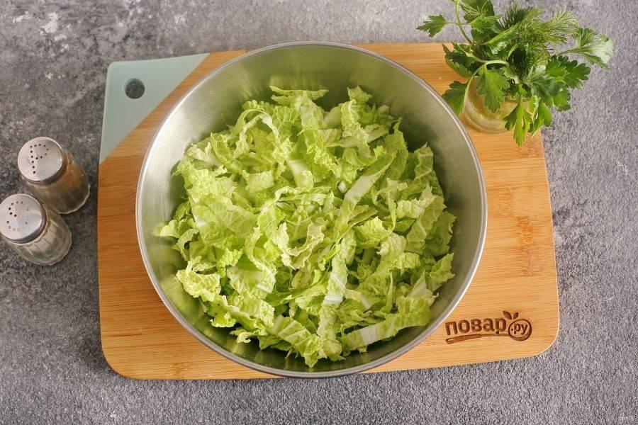 Куриное филе поставьте вариться в подсоленной воде (я варю после закипания 20-25 минут), а тем временем займемся остальными составляющими салата. Нашинкуйте капусту и переложите ее в глубокую миску.